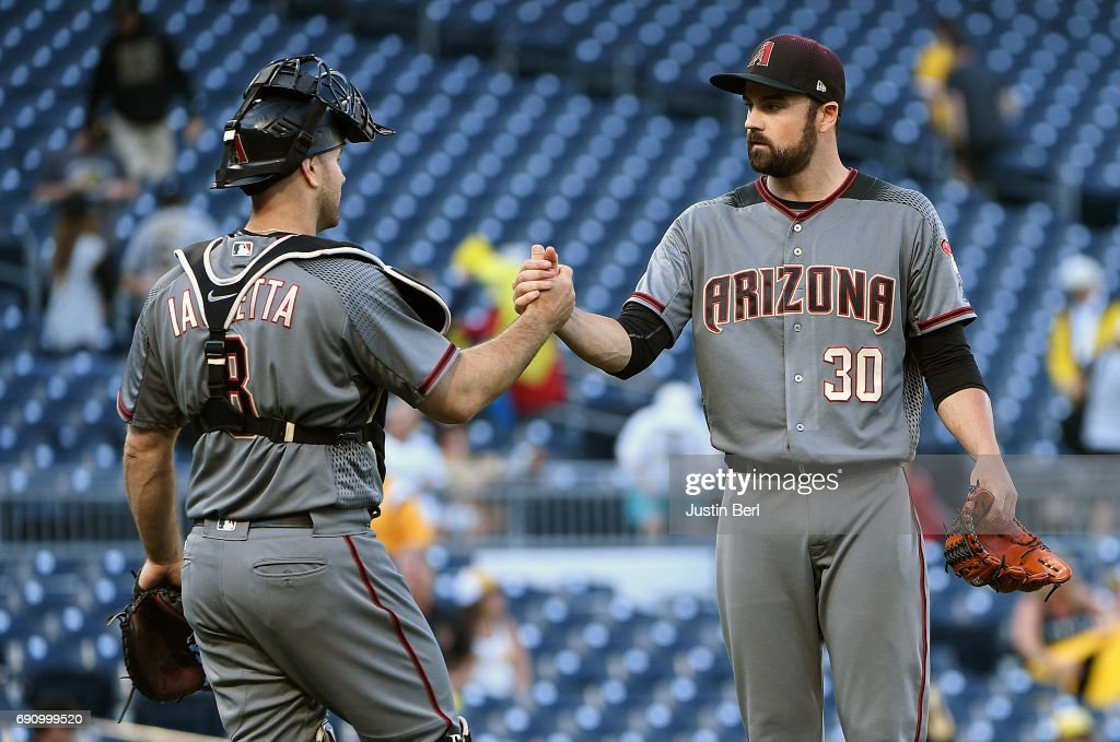 T.J. McFarland #30 of the Arizona Diamondbacks shakes hands with Chris Iannetta #8 after the final out in a 6-5 win over the Pittsburgh Pirates in 14 innings at PNC Park on May 31, 2017 in Pittsburgh, Pennsylvania.
