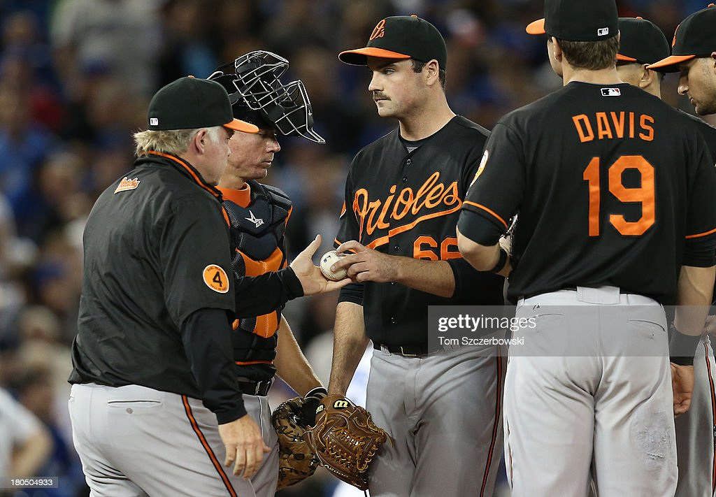 T.J. McFarland #66 of the Baltimore Orioles is relieved in the seventh inning by manager <a gi-track='captionPersonalityLinkClicked' href=/galleries/search?phrase=Buck+Showalter&family=editorial&specificpeople=208183 ng-click='$event.stopPropagation()'>Buck Showalter</a> #26 who makes a pitching change during MLB game action against the Toronto Blue Jays on September 13, 2013 at Rogers Centre in Toronto, Ontario, Canada.