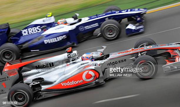 McLaren driver Jenson Button of Britain speeds through a corner with Williams driver Nico Hulkenberg of Germany during qualifying for Formula One's...