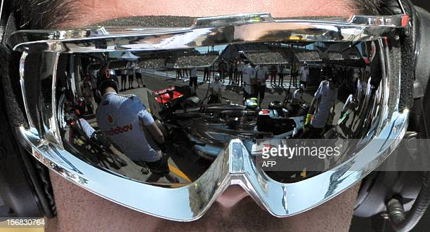 A McLaren Formula One car is reflected on the googles of a mechanic at Interlagos motorsport circuit in Sao Paulo on November 22 2012 ahead of the...