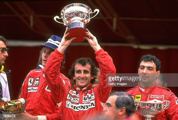 McLaren Honda driver Alain Prost of France holds the trophy aloft flanked by Scuderia Ferrari drivers Gerhard Berger of Austria and Michele Alboreto...