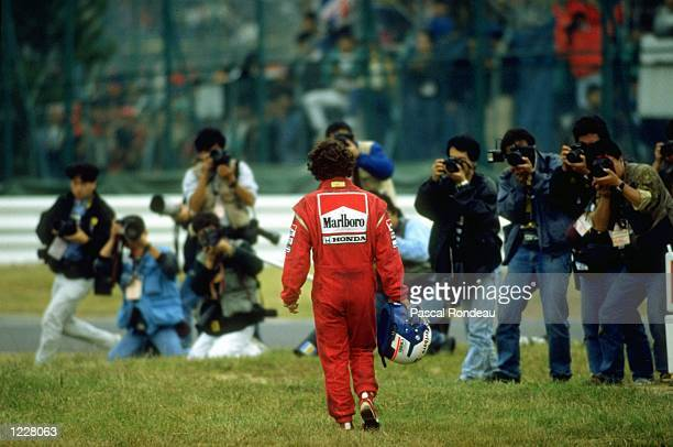 McLaren Honda driver Alain Prost of France walks back to the pits during the Japanese Grand Prix at the Suzuka circuit in Japan Prost retired from...