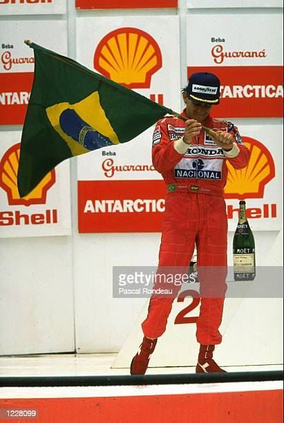 McLaren Honda driver Ayrton Senna of Brazil waves a flag as he stands on the winners'' podium after the Brazilian Grand Prix at the Interlagos...