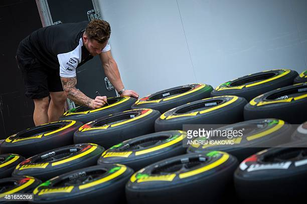 McLaren Honda's mechanic marks tires at the paddock at the Hungaroring circuit in Budapest on July 23 2015 prior to the weekend's Hungarian Formula...