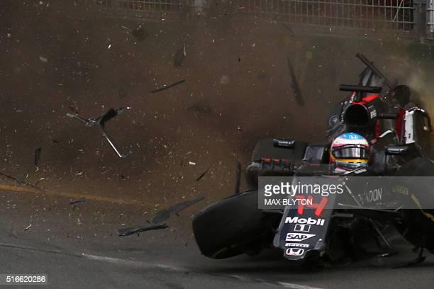 TOPSHOT McLaren Honda's Spanish driver Fernando Alonso crashes into the wall after colliding with Haas F1 Team's Brazilian driver Esteban Gutierrez...