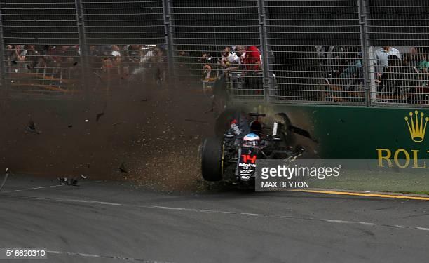 McLaren Honda's Spanish driver Fernando Alonso crashes into the wall after colliding with Haas F1 Team's Brazilian driver Esteban Gutierrez during...