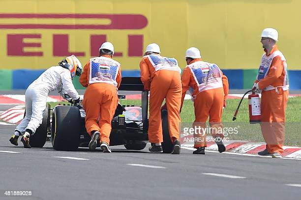 McLaren Honda's Spanish driver Fernando Alonso pushes his car after a trouble on the track during the qualifying session at the Hungaroring circuit...
