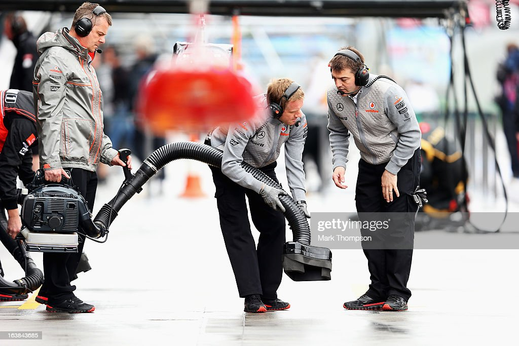 McLaren mechanics try to dry their pitstop area before the weather delayed qualifying session for the Australian Formula One Grand Prix at the Albert Park Circuit on March 17, 2013 in Melbourne, Australia.
