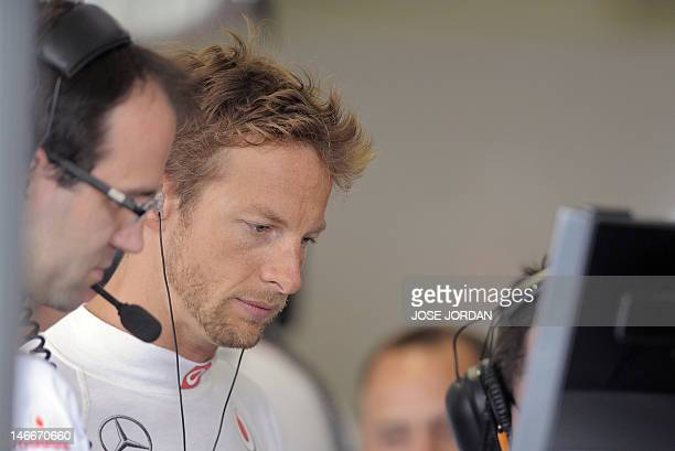 McLaren Mercedes' British driver Jenson Button looks at a control screen in the pits at the Valencia Street Circuit on June 22 2012 in Valencia...