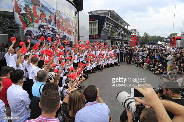 McLaren Mercedes' team poses in the paddock to celebrate the 50th birthday since Bruce McLaren Motor Racing Ltd was created at the Autodromo...