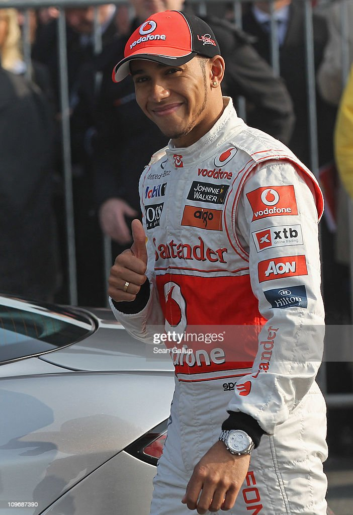 McLaren race car driver <a gi-track='captionPersonalityLinkClicked' href=/galleries/search?phrase=Lewis+Hamilton+-+Racecar+Driver&family=editorial&specificpeople=586983 ng-click='$event.stopPropagation()'>Lewis Hamilton</a> gestures before climbing into a Mercedes-Benz McLaren car prior to give rides to Vodafone corporate clients at the CeBIT technology trade fair on March 1, 2011 in Hanover, Germany. CeBIT 2011 will be open to the public from March 1-5.