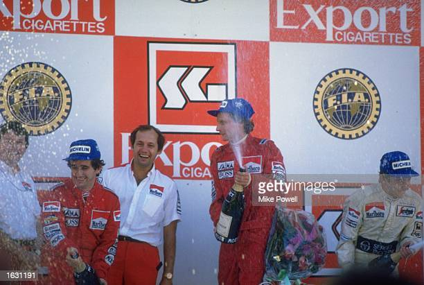 McLaren TAG drivers Alain Prost and Niki Lauda of Austria partake in the traditional champagne celebration after the Portuguese Grand Prix at the...