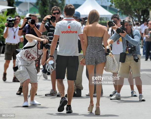 McLarenMercedes driver Jenson Button of Britain holds hands with his girlfriend Jessica Michibata while photographers take picture upon their arrival...