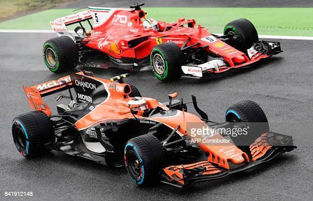 McLaren's Belgian driver Stoffel Vandoorne competes with Ferrari's German driver Sebastian Vettel during the qualifying session at the Autodromo...
