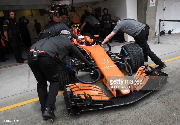 McLaren's Belgian driver Stoffel Vandoorne is pushed back into his pit garage during a practice session ahead of the Formula One Chinese Grand Prix...