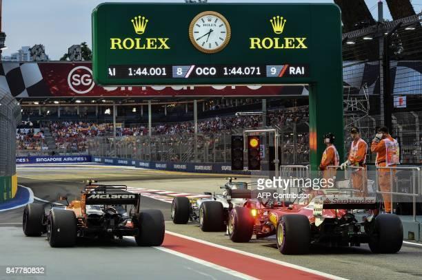 McLaren's Belgian driver Stoffel Vandoorne Mercedes' Finnish driver Valtteri Bottas and Ferrari's German driver Sebastian Vettel prepare to leave the...