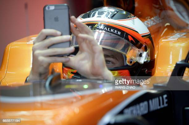 McLaren's Belgian driver Stoffel Vandoorne uses a mobile phone to take a picture in the pit during the second practice session ahead of the Formula...