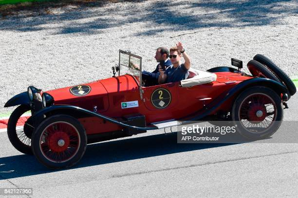 McLaren's Belgian driver Stoffel Vandoorne waves as he drives in a historical car during a car parade ahead of the Italian Formula One Grand Prix at...