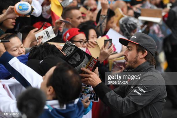 McLaren's Spanish driver Fernando Alonso signs autographs for fans in Shanghai on April 6 ahead of the Formula One Chinese Grand Prix / AFP PHOTO /...