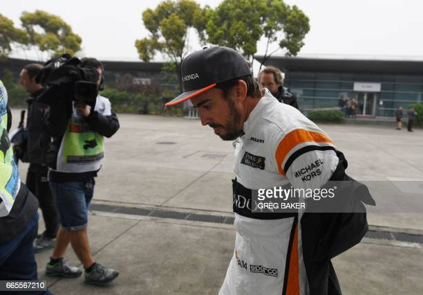 McLaren's Spanish driver Fernando Alonso walks to his pit garage during a practice session ahead of the Formula One Chinese Grand Prix in Shanghai on...