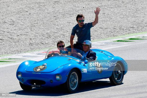 McLaren's Spanish driver Fernando Alonso waves from a historical car during a car parade ahead of the Italian Formula One Grand Prix at the Autodromo...