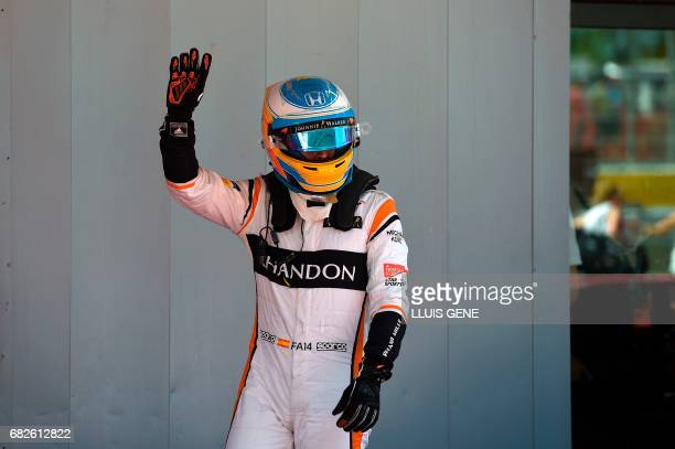 McLaren's Spanish driver Fernando Alonso waves in the parc ferme after the qualifying session at the Circuit de Catalunya on May 13 2013 in Montmelo...