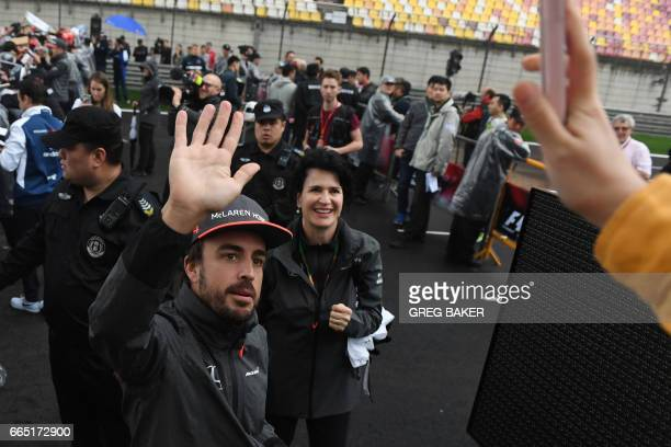 McLaren's Spanish driver Fernando Alonso waves to fans during a fan event in Shanghai on April 6 ahead of the Formula One Chinese Grand Prix / AFP...