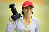 A lady with red cap holding a DSLR camera with smiling face.