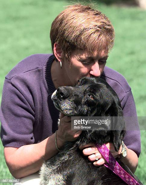 MEAdoptdog1BG27Apr98––Carol Bills gives a pet kiss and a hug to the mix lab Oscar that was found last month in a trash dumpster Bills has adopted the...