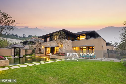 meadow near pond in modern buildings at twilight : Stock Photo
