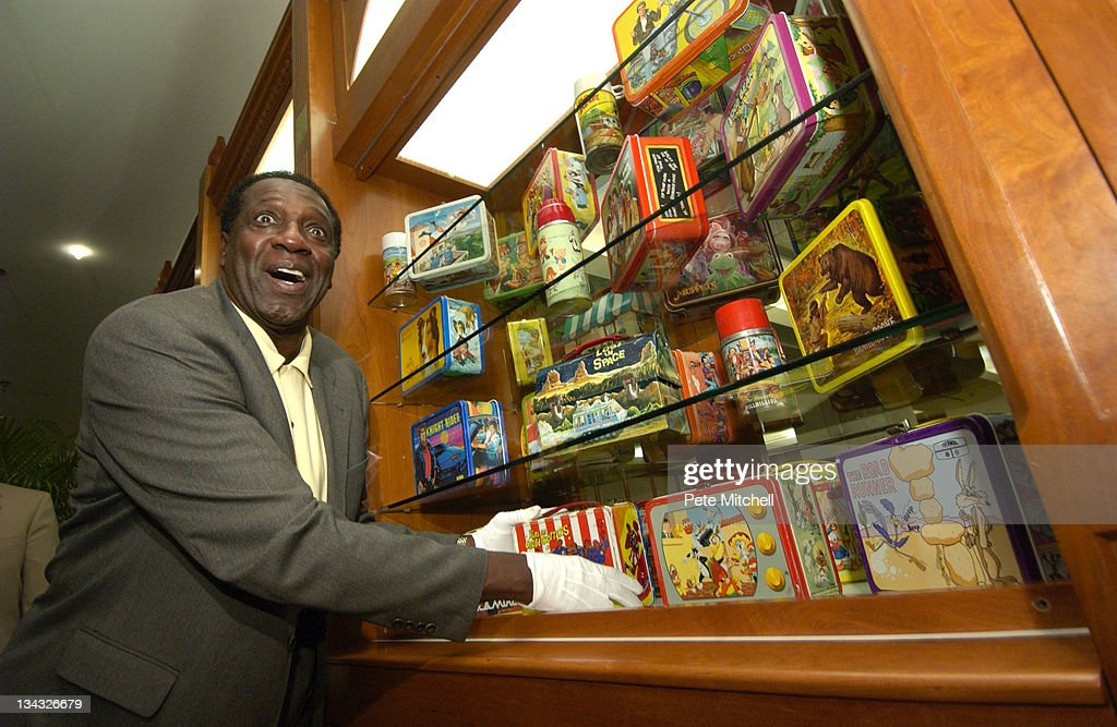 Meadowlark Lemon of the Harlem Globetrotters places the Harlem Globetrotters lunchbox into the 'Taking America to Lunch' display, which opens today at the museum.