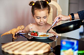 Mother puts potato pancakes on a plate to a daughter