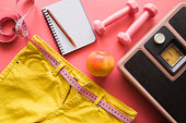 Measure tape with yellow jeans, dumbbells, weight scale, apple, notebook on a pink background. Women diet before summer season. Healthy lifestyle, body slimming, weight loss concept. Cares about body.