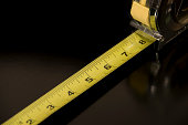 A close up of a tape measure isolated on a black background.