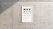 Measurement table of sight. Framework hanging on a concrete wall. View examination. Letters in block letters. Eye test. Visual Acuity