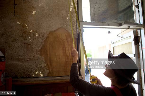 Measurements are made to repair the front window at Belle Hardware by a neighborhood clean up crew that arrived to help out the morning after...