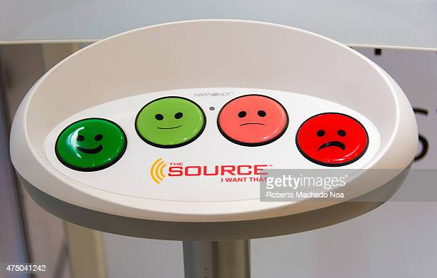 Measuring customer satisfaction in store Colorful buttons with smiley faces on a white plastic device with the words 'The Source I Want That' written...