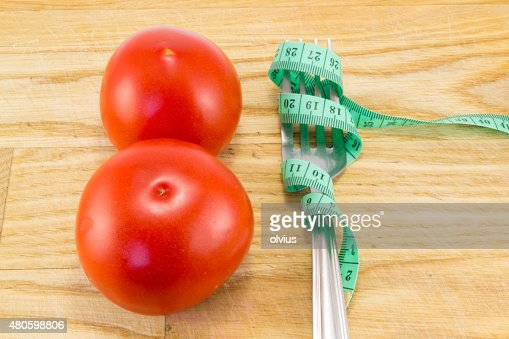 Measuring tape and a fork with tomato isolated : Stock Photo