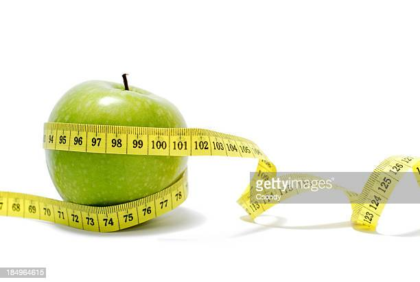 A measuring tape around a Granny Smith Apple isolated