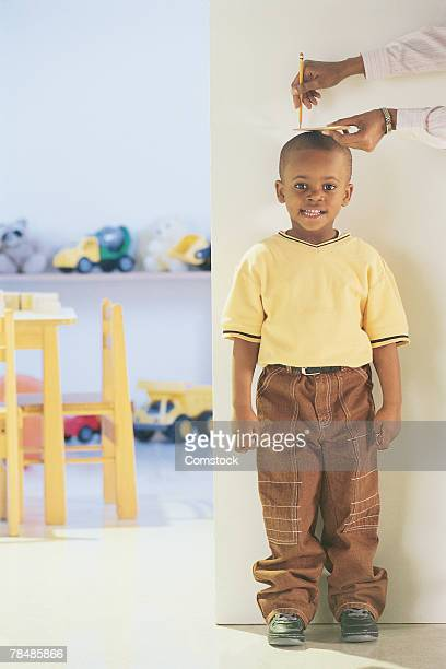 Measuring young boy's height on wall