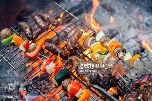 Meat and veggies cooking over campfire : Stock Photo