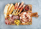 Meat appetizer selection or wine snack set. Variety of smoked meat, salami, prosciutto, bread sticks, baguette, olives and sun-dried tomatoes on rustic wooden board, top view, horizontal