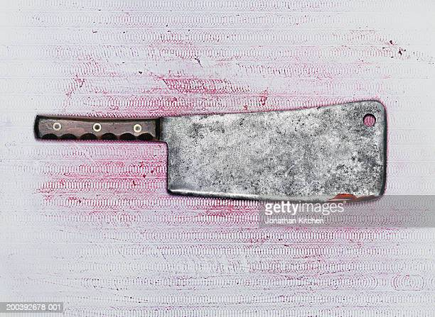 Meat cleaver covered in blood on chopping board