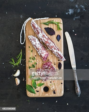 Meat gourmet snack. Salami, garlic and herbs on rustic wooden : Stock Photo