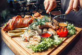 Meat on a wooden tray with roasted vegetables and sauce top view fine dining