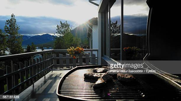 Meat On Barbecue Grill In Balcony Against Sky