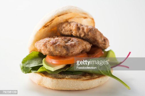Meat patties with spinach and avocado in hamburger roll : Stock Photo