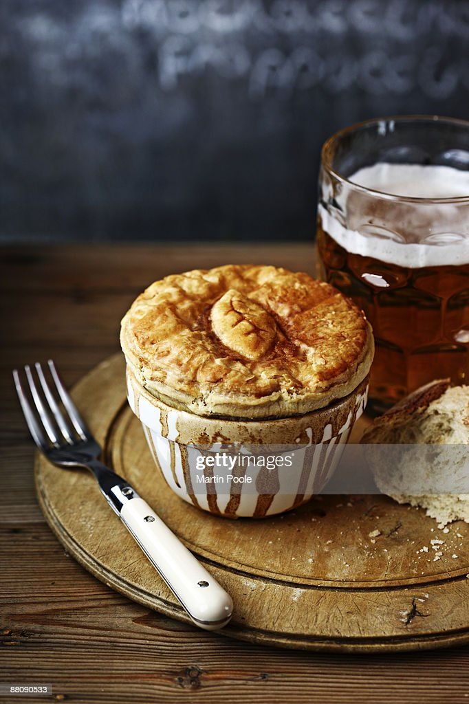 meat pie on bread board with pint of bitter : Stock Photo