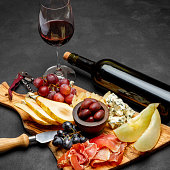 Meat plate antipasti snack with Prosciutto ham, blue cheese, melon, grapes, Olives on wooden serving board