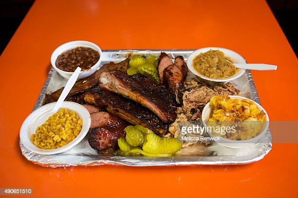 A meat platter with fried corn baked beans sauerkraut macaroni and cheese spare ribs pulled pork smoked polish sausage brisket fire and ice and bread...